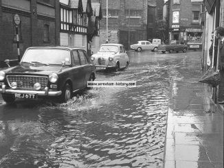 a-morris-1100-and-an-austin-a35-negotiating-flooding-mount-street-wrexham-july-1965