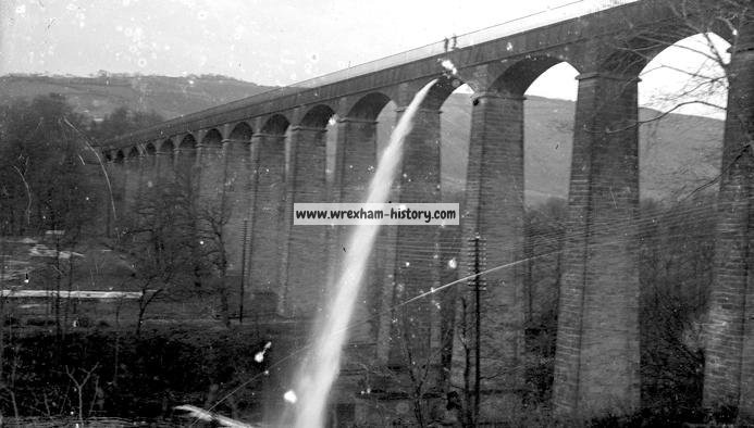 a black and white photo of a large aqueduct being drained